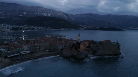 paisagem urbana : aerial view of coastal old town Budva with medieval buildings at dusk