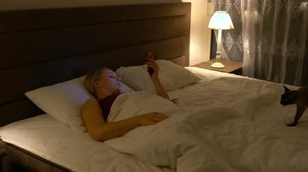 noc : young woman lies in bed in the company of a cat and uses a smartphone Wideo