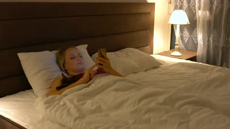 noc : young woman lies in bed and uses a smartphone in the evening