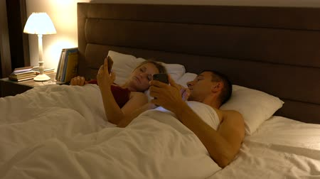 objetí : couple lies in bed and use smartphones