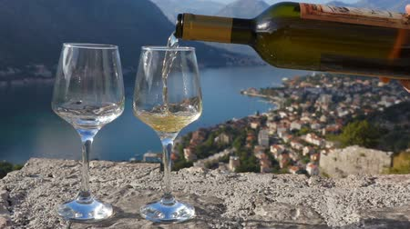 paisagem urbana : white wine is poured into a glass against the backdrop of the bay Vídeos