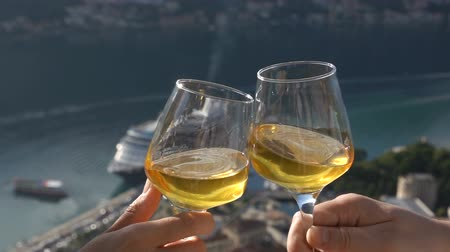 sobre o branco : two glasses of white wine touch each other on the background of the bay