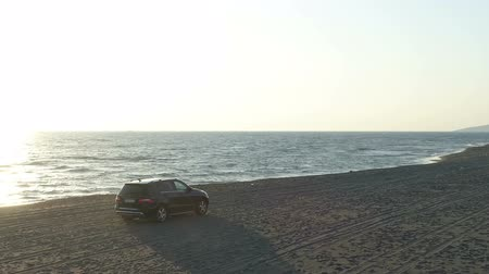 랠리 : aerial view of a car moving along a sandy beach along the sea