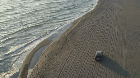 ралли : aerial view of a car moving along a sandy beach along the sea