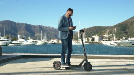mobilet : Handsome business guy unlocks the electric scooter using the application on a smartphone and leaves on business Stok Video