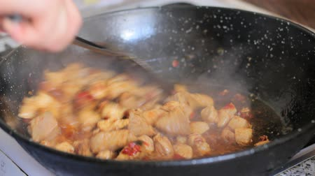 warzywa : Frying chicken to make a traditional spanish paella