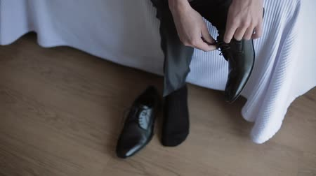 cadarço : Groom sitting on bed and tying dress shoes for wedding ceremony
