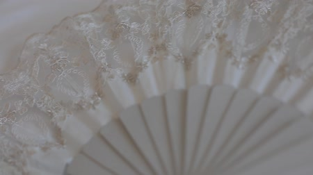 koronka : White wedding fan for the bride. Panning shot.