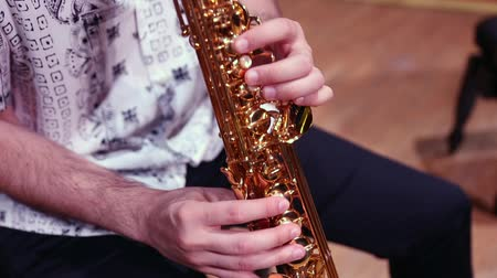 saxofone : Close up of the hands of a man with exotic shirt playing saxophone in a stage Stock Footage