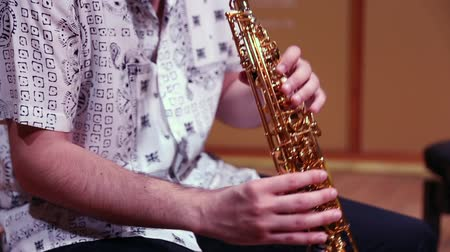 sassofono : A man in a stylish white shirt emotionally plays the soprano saxophone. Close-up.