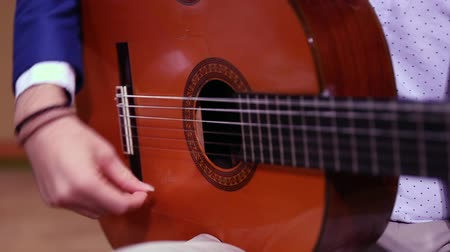 kytarista : Close-up of musician hands playing classical spanish acoustic guitar. Focus on hand.