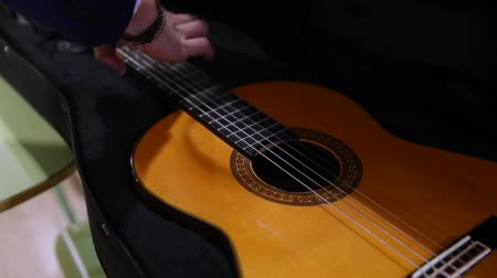 flamenco : Close-up of musician opening a black case and taking a classical spanish acoustic guitar.