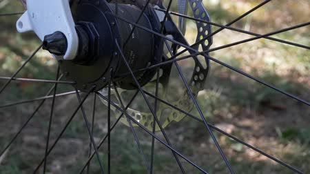 motorcar : Modern bicycle tire with electric wheel led light and motor on the blurry background, outside in the summer day Stock Footage
