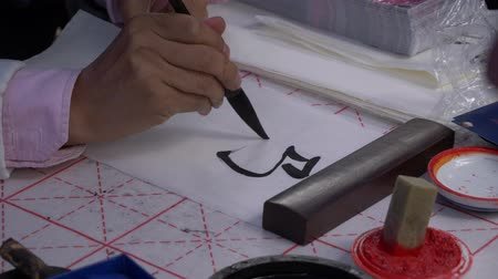 タイプスクリプト : Slow motion, close-up shot of hand using a large ink brush to write traditional Japanese calligraphy