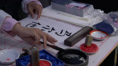 hieroglifa : Slow motion, close-up shot of hand using a large ink brush to write traditional Japanese calligraphy