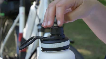 durável : Hand takes black plastic cap from stainless steel insulated white bottle in new bicycle in background close-up 4K video Stock Footage