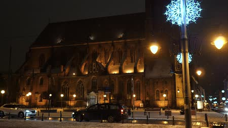 kardan adam : Beautiful Snowfall at night. White Winter in Wroclaw, Poland. St. Mary Magdalene Church Christmas lights moving cars and taxi