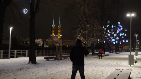 step : Beautiful Snowfall. White Winter in Wroclaw, Poland. Cathedral of St. John. Street with Christmas lights
