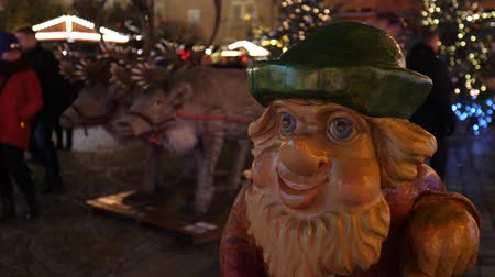 törpe : Christmas market at night time in Europe. Christmas tree in background with lights. Colourful gnome dwarf decoration, happy family time