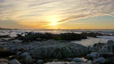 seixo : Slow motion pan right Pacific Ocean Waves rolling in and break on a rocky coast under a sunset sky at Pacific Grove, California on the Monterey Peninsula at stormy weather
