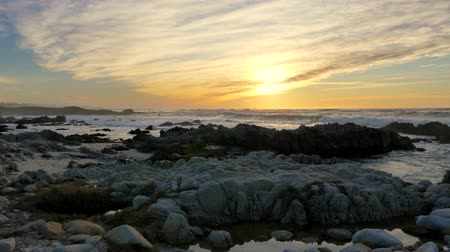 seixo : Slow motion Pacific Ocean Waves rolling in and break on a rocky coast under a sunset sky at Pacific Grove, California on the Monterey Peninsula at stormy weather