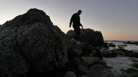 trabalhar fora : Men practicing relaxation technique walking on the rocky pacific coast