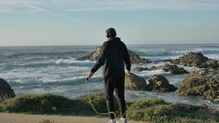 velkolepý : Men whearing headphones then Skipping training at the pacific coast with magnificent waves at sunny day working out is healthy fitness body Dostupné videozáznamy