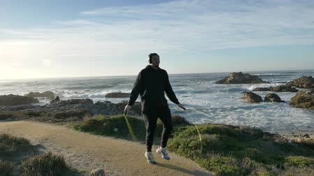 velkolepý : Men with headphones Skipping training at the pacific coast with magnificent waves at sunny day working out is healthy fitness body