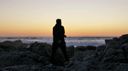 persone : Men practicing on the rocky stones horizon at sunset or sunrise. Art of self-defense. Silhouette on a background of dramatic epic waves at pacific coast