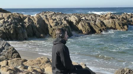 persone : Men in headphones practicing yoga at pacific ocean rocky coast with magnificent waves