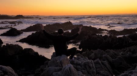 barışçı : Men warrior monk practicing silhouette tai chi karate kung Fu on the rocky stones horizon at sunset or sunrise. Art of self-defense. Silhouette on a background of dramatic epic waves at pacific coast