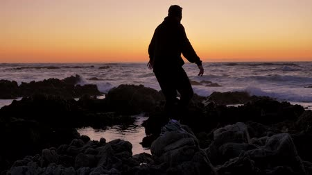 persone : Men warrior monk practicing silhouette tai chi karate kung Fu on the rocky stones horizon at sunset or sunrise. Art of self-defense. Silhouette on a background of dramatic epic waves at pacific coast
