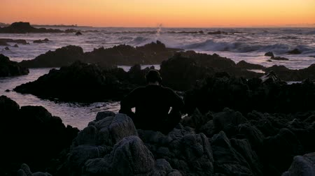 chi : Men in headphones practicing yoga at pacific ocean rocky stones horizon at sunset or sunrise. Art of self-defense. Silhouette on a background of dramatic epic waves at pacific coast