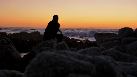 Men Relaxing on the rocks watching sunset at pacific coast Stock Footage