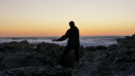 мастер : Men warrior monk practicing silhouette tai chi karate kung Fu on the rocky stones horizon at sunset or sunrise. Art of self-defense. Silhouette on a background of dramatic epic waves at pacific coast