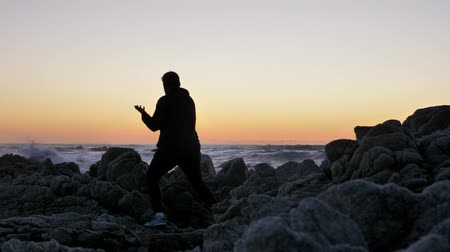 Men warrior monk practicing silhouette tai chi karate kung Fu on the rocky stones horizon at sunset or sunrise. Art of self-defense. Silhouette on a background of dramatic epic waves at pacific coast
