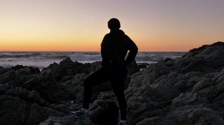 Men watching red sunset. Silhouette on a background of dramatic epic waves at pacific coast Стоковые видеозаписи