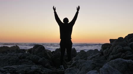 Men practicing yoga on the rocky stones horizon at sunset or sunrise. Art of self-defense. Silhouette on a background of dramatic epic waves at pacific coast