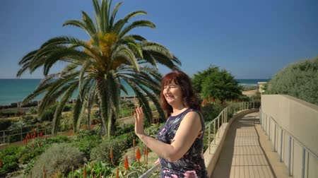 Happy woman waving to friends in Linda Lane Park in San Clemente California