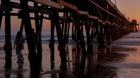 Couple walking holding hands together at Scenic orange pink Sunset with epic rays of light and sun flare under wooden pier in San Clementa California Stock Footage