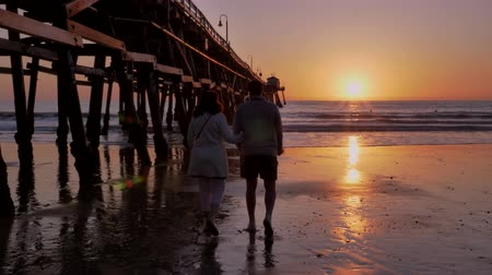 Couple walking away holding hands together at Scenic orange pink Sunset with epic rays of light and sun flare wooden pier in San Clementa California