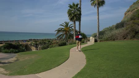 A handsome, young guy, a man in a navy blue shirt with and shorts is walking along in California coast San clemente Linda Lane park Стоковые видеозаписи