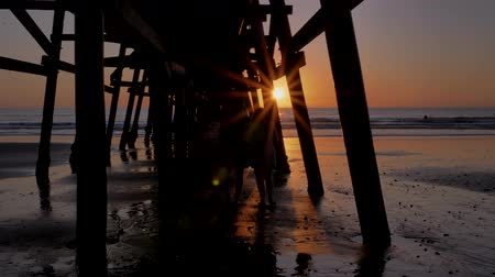 megye : Couple walking away holding hands together at Scenic orange pink Sunset with epic rays of light and sun flare wooden pier in San Clementa California