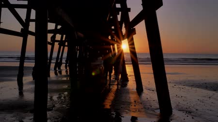 Couple walking wide shot holding hands together at Scenic orange pink Sunset with epic rays of light and sun flare wooden pier in San Clementa California Stock Footage
