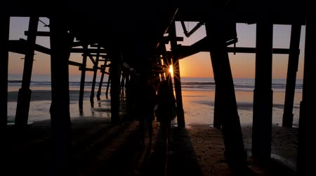 Couple walking close holding hands together at Scenic orange pink Sunset with epic rays of light and sun flare wooden pier in San Clementa California