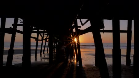 Couple walking holding hands together at Scenic orange pink Sunset with epic rays of light and sun flare wooden pier in San Clementa California