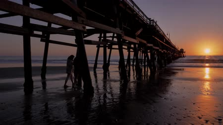 megye : Couple walking together holding hads Scenic orange pink Sunset with epic rays of light and sun flare wooden pier in San Clementa California