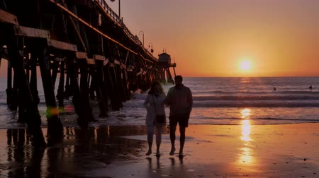 Couple walking at Scenic orange pink Sunset with epic rays of light and sun flare wooden pier in San Clementa California