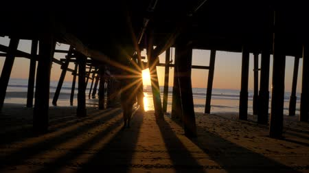 megye : Woman silhouette walking under pier at Scenic orange pink Sunset with epic rays of light and sun flare wooden pier in San Clementa California