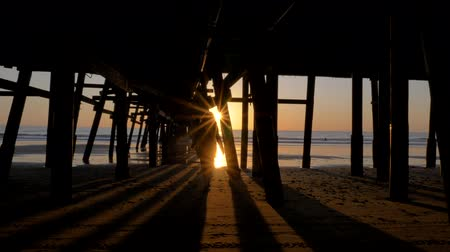 Woman silhouette walking under pier at Scenic orange pink Sunset with epic rays of light and sun flare wooden pier in San Clementa California